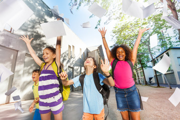 Kids throw paper in the air with sheets flying