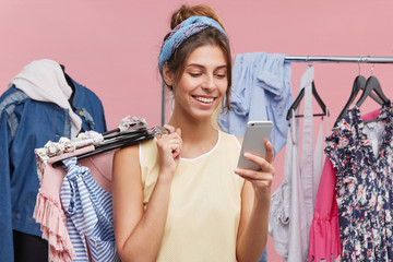 Happy female standing at clothing store, messaging with friend over smart phone while trying new clothes asking for advice what to buy. Cheerful woman using modern cell phone in shopping mall.