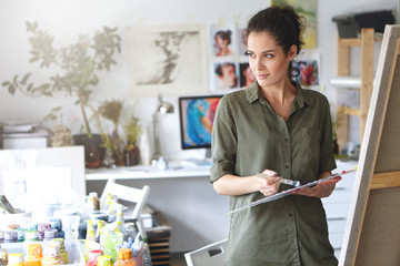 Serious attractive female painter with dark hair, wearing casual shirt, standing in her workshop, holding paintbrush in her hands, using watercolors for painting picture. Creative person painting