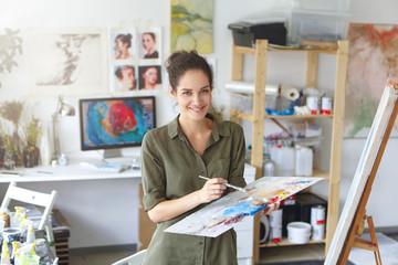 Picture of cheerful successful young female artist of European appearance looking at camera with charming happy smile, holding palette and brush, finishing work on large painting. People and job