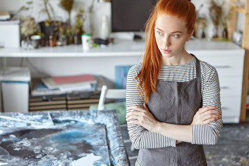 Beautiful red haired female wearing apron, keeping hands crossed, looking pensively aside while standing in workshop, resting for minute after creating masterpiece. Creative ginger young woman