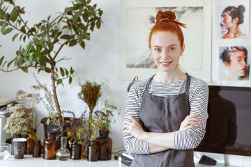 Lovely ginger female studying art in workshop, smiling gently in camera, standing crossed hands against beautiful pictures. Woman with red knot wearing apron going to creat something original