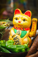Chinese golden lucky cat figurine on food street stall, green peppers