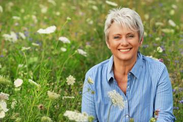 Glückliche Seniorin sitzt entspannt in einer  Sommerwiese