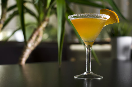 Cocktail sidecar on black table with palm tree on background