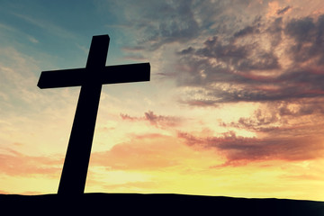 Religious cross silhouette against a bight sunrise sky. 3D Rendering