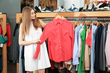 Young woman choosing shirt in mall