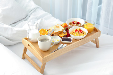 Delicious sweet breakfast with coffee on bed