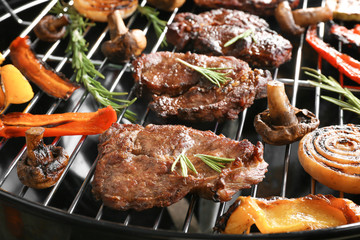 Tasty steaks and vegetables on barbecue grill, close up