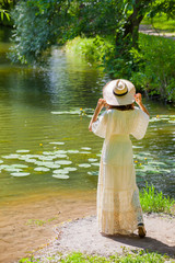 girl in a white dress and hat on the shore of a pond with water-lilies