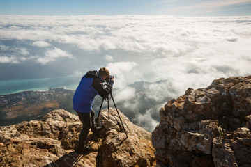 Man standing with a tripod and camera on a high mountain peak above clouds, city and sea. Professional photographer adjusting dslr settings on rocky summit.