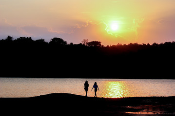 Silhouette lovely couple standing and looking silhouette view of lake and mountain in sunset or sunrise. Sunshine with landscape view and traveler in twilight time.