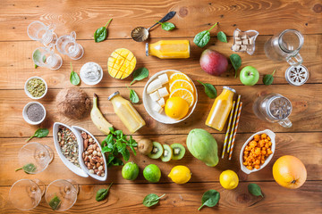 Variety of fresh fruits, seeds and nuts for healthy eating or making yellow or green smoothie over old rustic wooden background, top view. Healthy eating,