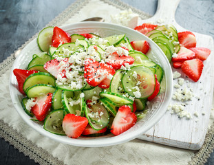 Summer Cucumber and strawberry salad topped with nigella seeds and feta cheese