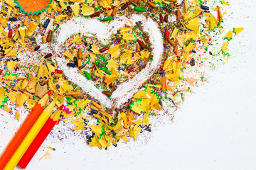 heart, multicolored pencils and varicolored wooden shavings