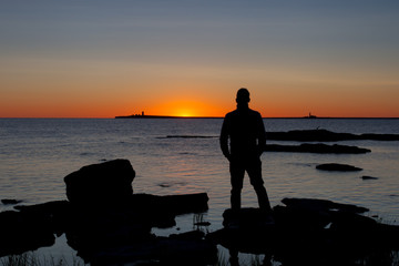 Silhouette human watching the sunrise. The island of Gotland in the Baltic sea.