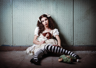 Portrait of strange lonely girl with dolls in abandoned place