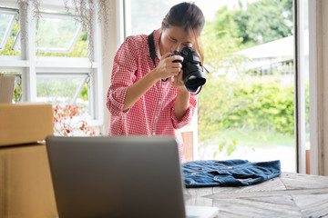 business owner take photo of her product for selling on website. freelance woman seller holding digital camera and take picture of cloth. Online selling, internet marketing, e-commerce concept