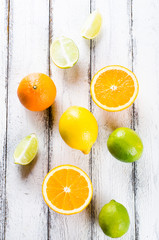 Fresh citrus fruits on white rustic wooden background view from above