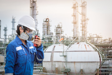 technician with gas mask against petrochemical plant
