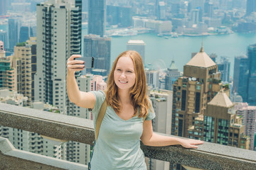 Hong Kong Victoria Peak woman taking selfie stick picture photo with smartphone enjoying view over Victoria Harbour. Viewing platform on top of Peak Tower, HK. Defocused background.Travel asia concept