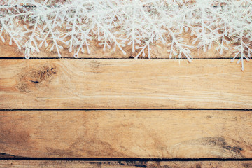 Wooden brown christmas background and snowflakes with space.