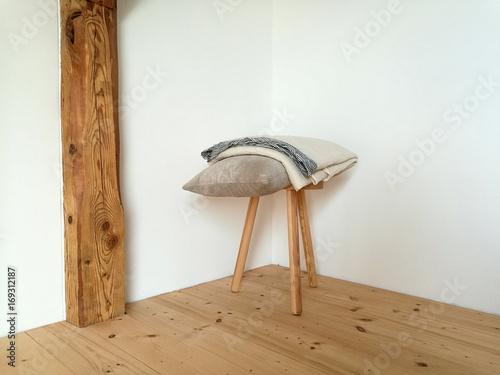 Schemel mit Kissen und Decke im Schlafzimmer eines rustikalen ...