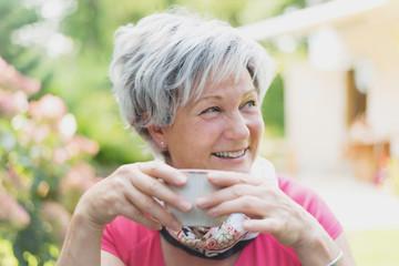 reifere Frau hält eine Kaffetasse in der Hand und lacht
