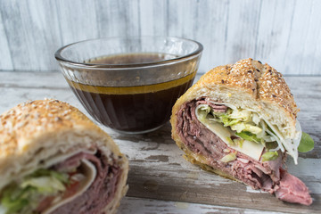 roastbeef sandwich with bowl of beef broth for dipping closeup