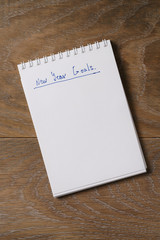 new year goals tempate with notepad on wood table