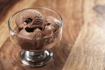 chocolate ice cream in glass bowl on wooden table