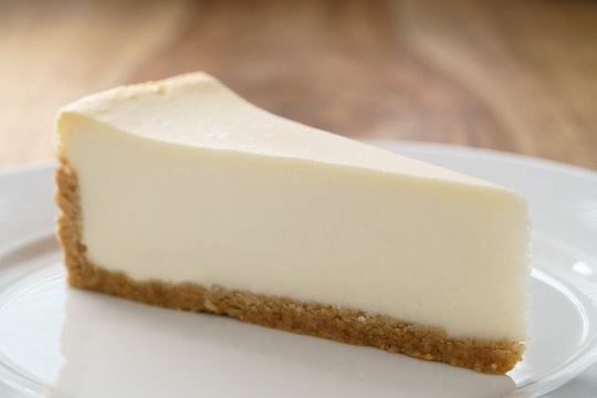 slice of traditional new york cheesecake on white plate on wood table