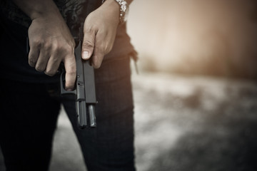 Robber holding gun for ready to murder steal moneys at abandoned building. Selective focus. criminality and social issues concept. Dark and low key tone tone pinterest and instragram like process.