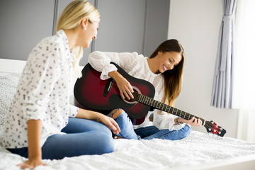 Two young women with guitar on bed