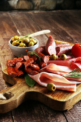 Marble cutting board with prosciutto, bacon, salami and sausages