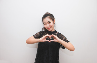 Asian woman making a heart sign with her hands, body language
