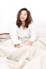 Beautiful woman waking up in her bed in the bedroom, she is smiling after wake up.
