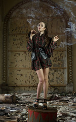 A beautiful girl, a model in a refined outfit in a creative location smokes a pipe. Fashion, style, beauty, portrait.