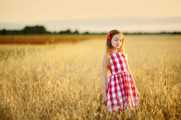 Adorable girl walking happily in wheat field on warm and sunny summer evening