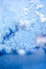 festive background of blue ice on window, close up