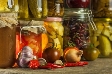 Jars with variety of pickled vegetables. Carrots, field garlic, parsley in glas. Preserved food. Fermented preserved vegetarian food concept.