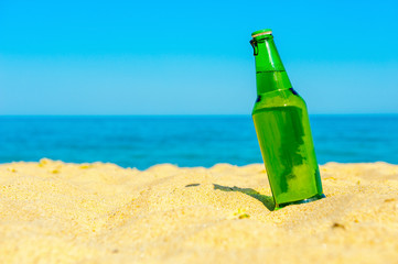 bottle of fresh beer costs on the beach in sand, on a background the sea