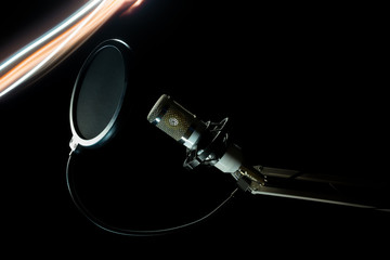 Professional condenser studio microphone on the black background and freezelight