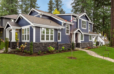 Beautiful, Newly Built Luxury Home Exterior with Green Lawn, and Forest in Background