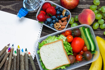 school lunch boxes with sandwich, fruits, vegetables and bottle of water with colored pencils and empty copybook