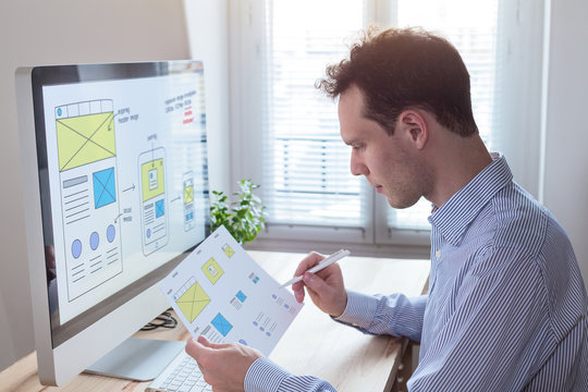 Website designer reading client specification, sketching responsive wireframe layout design