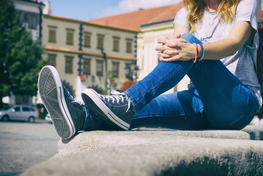 Young girl sitting on city fountain dressed in jeans and sneakers