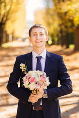 Portrait of a groom holding wedding bouquet in the autumn park