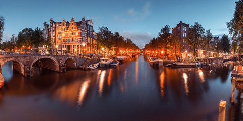 Photo sur Toile Amsterdam Panorama of Amsterdam canal, bridge and typical houses, boats and bicycles during evening twilight blue hour, Holland, Netherlands. Used toning