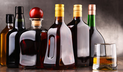 Glass and bottles of assorted alcoholic beverages.